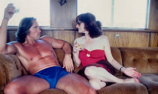 arnold sitting on couch with woman arnold is not wearing shirt