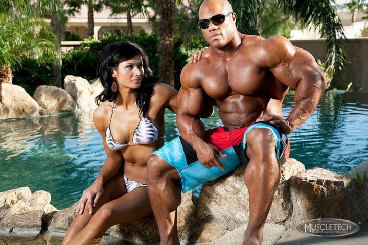 bodybuilder on beach with girl