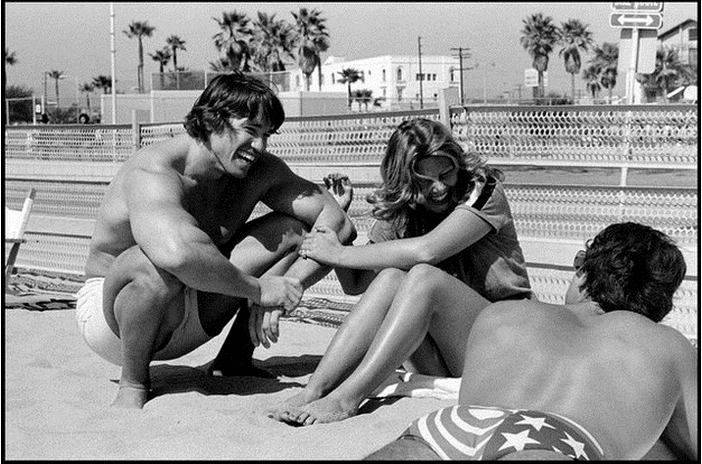 vintage photo of arnold on beach with girl and frank zane