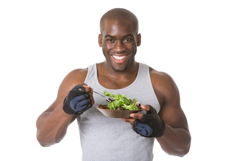 Bodybuilder eating a bowl of salad